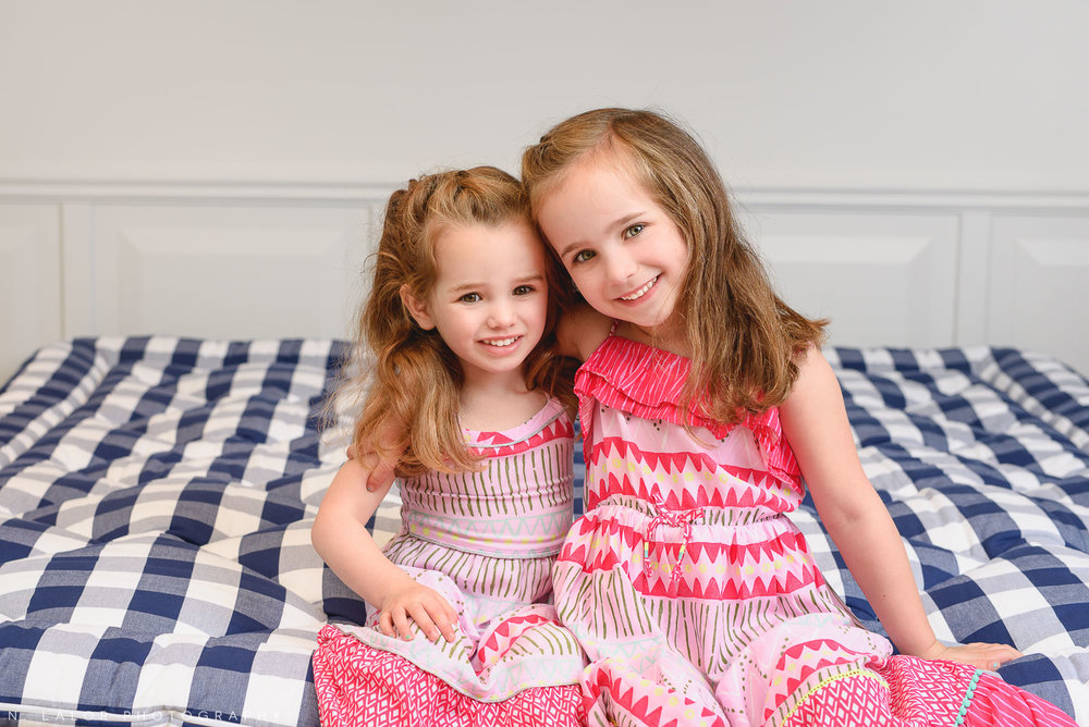 Sisters sitting together on a luxury bed. Limited-edition exclusive event with N. Lalor Photography and Hästens in Greenwich, Connecticut.