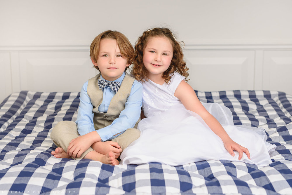 Brother and Sister sitting on a high-end bed. Limited-edition exclusive event with N. Lalor Photography and Hästens in Greenwich, Connecticut.