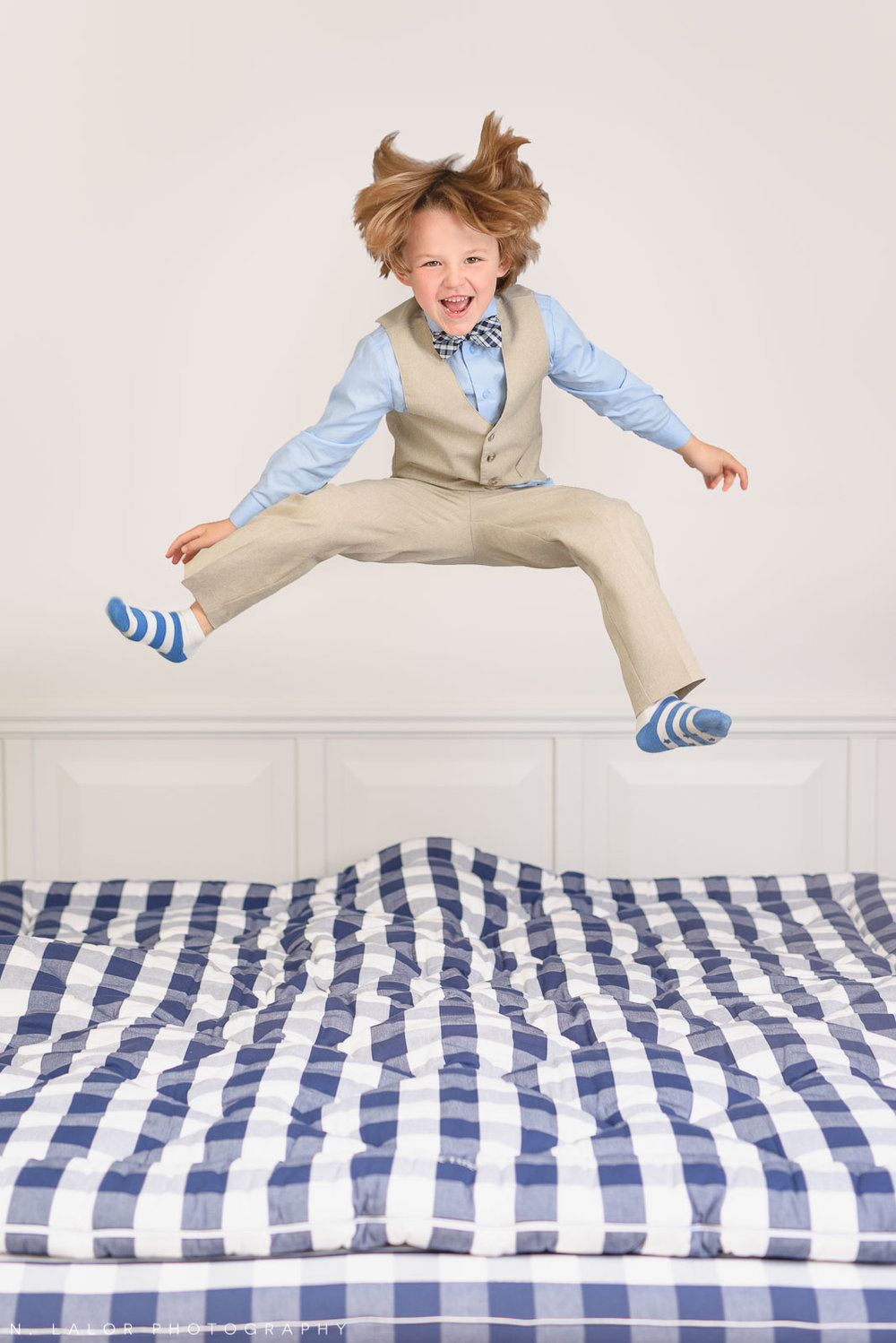 Boy having fun jumping on a Hästens bed. Limited-edition exclusive event with N. Lalor Photography and Hästens in Greenwich, Connecticut.