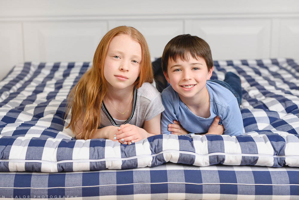 Siblings lounging on a luxury mattress. Limited-edition exclusive event with N. Lalor Photography and Hästens in Greenwich, Connecticut.