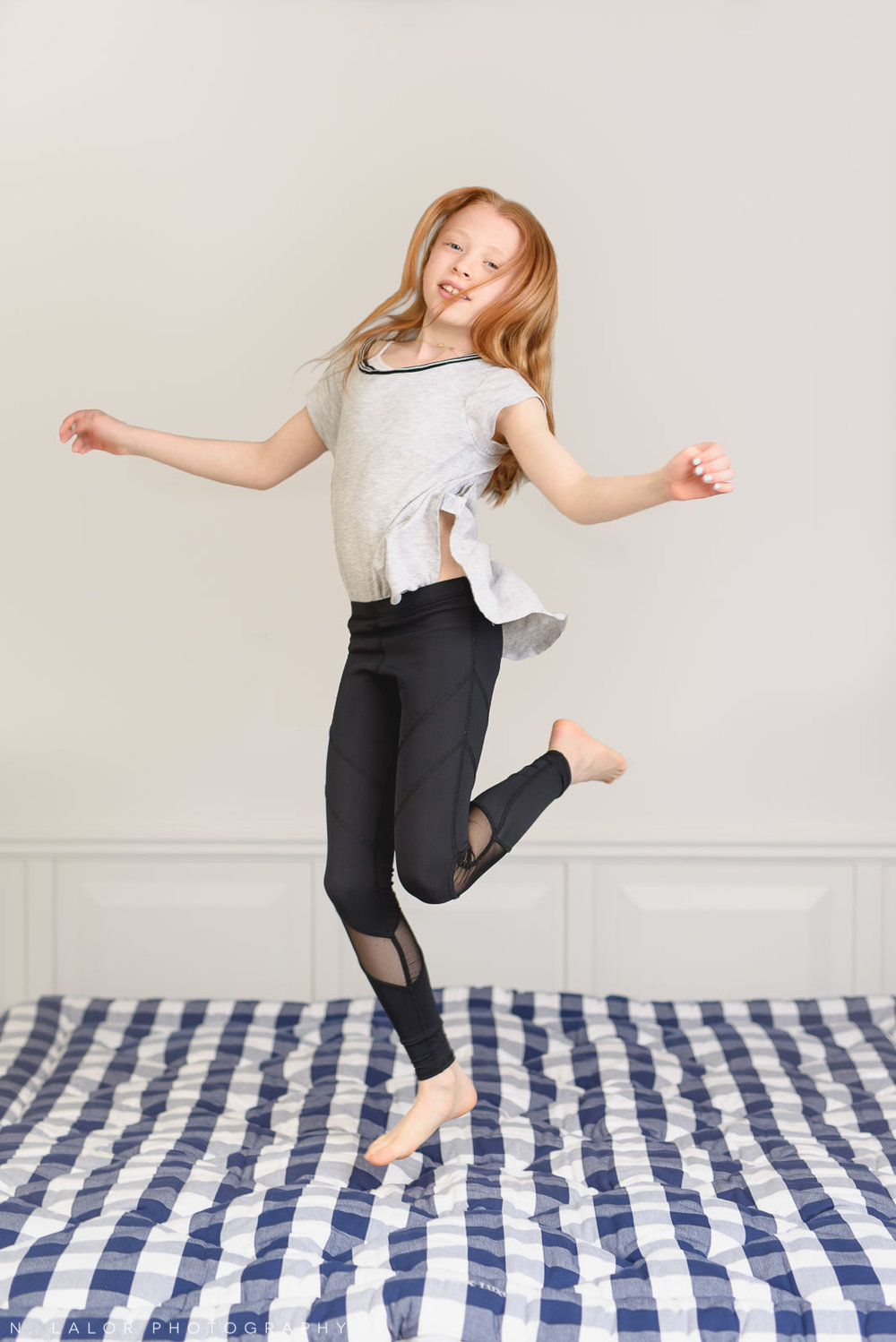 Girl having fun jumping on a Hästens bed. Limited-edition exclusive event with N. Lalor Photography and Hästens in Greenwich, Connecticut.