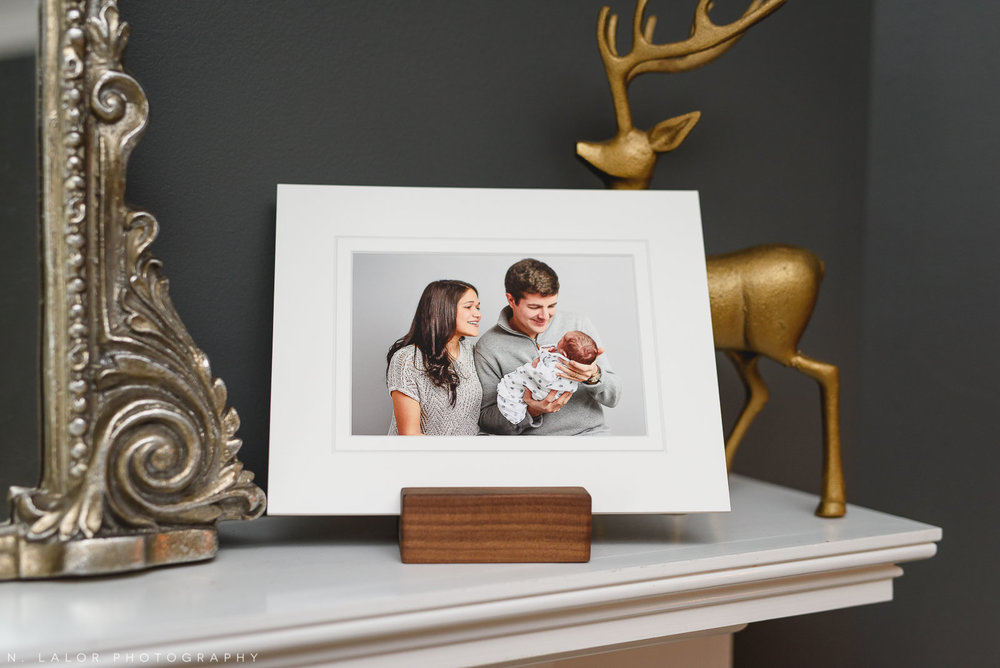 Photograph of a fine art print of mom and dad with their newborn baby by N. Lalor Photography. Greenwich Connecticut photo Studio.