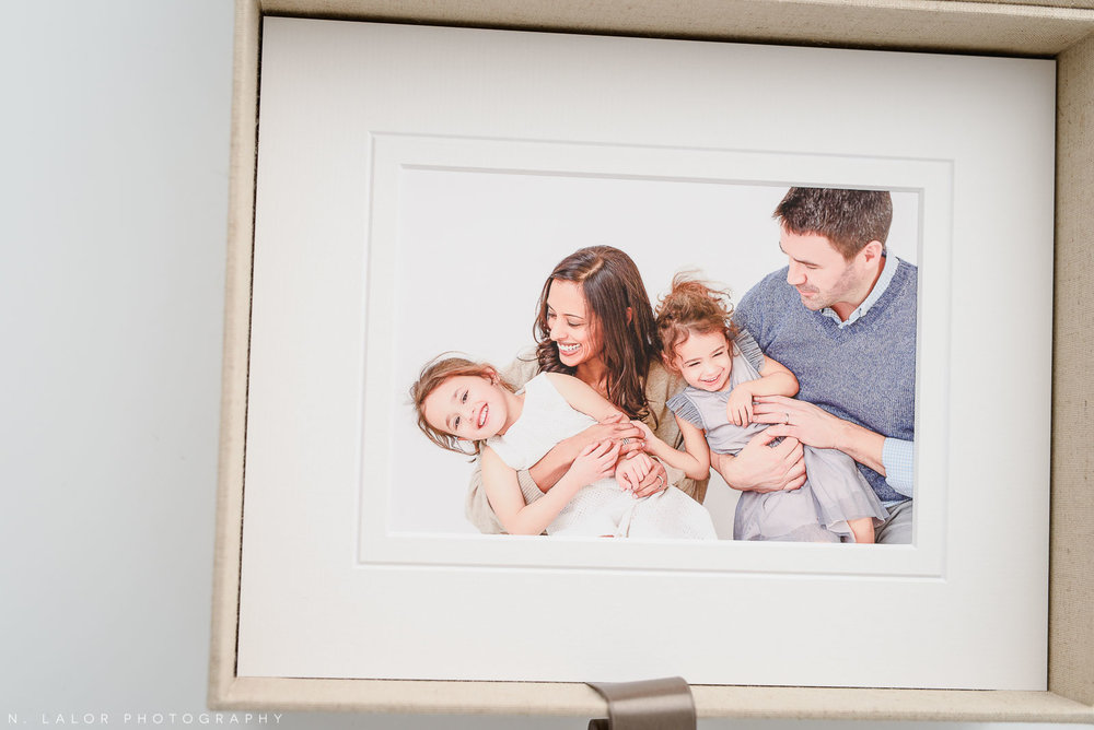 Photograph of a family laughing together with their two young girls, printed and beautifully matted. Image by N. Lalor Photography, Greenwich Connecticut.