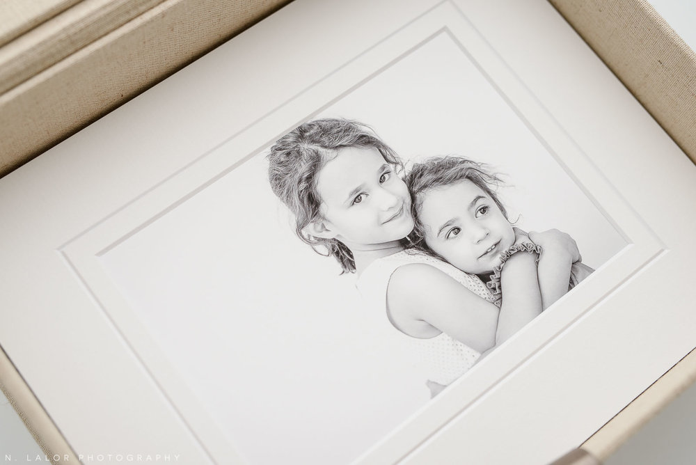 Studio photograph of two sisters hugging, printed and beautifully matted. Image by N. Lalor Photography, Greenwich Connecticut.