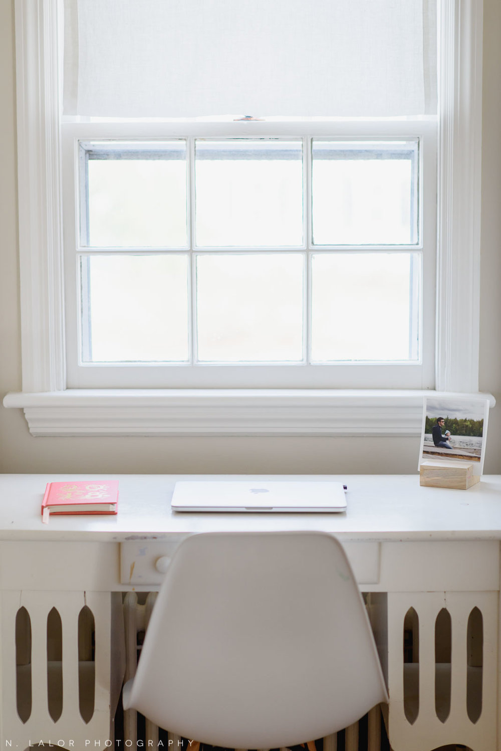 Image of a home office desk with a laptop and photo prints in wood block. Photograph by N. Lalor Photography.