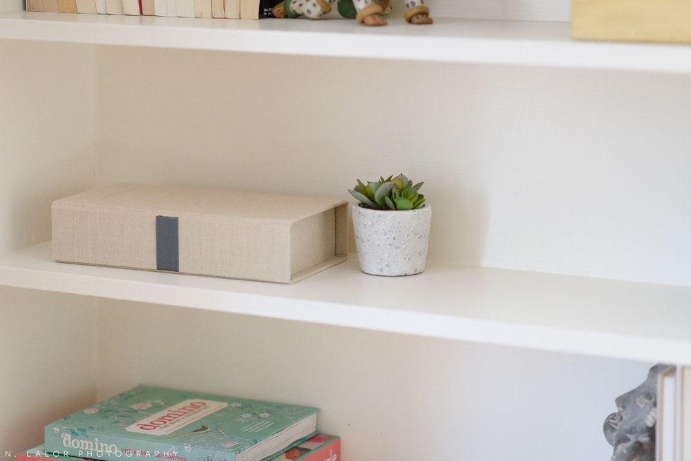 Image of an open shelf display, showing a memory box for a child. Photograph by N. Lalor Photography.