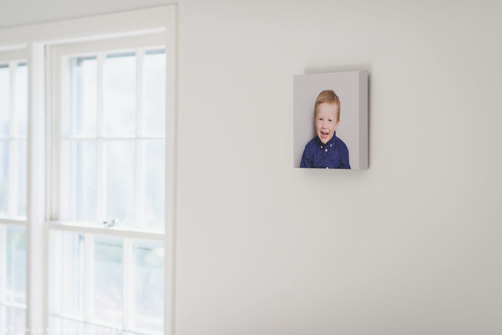 A small canvas on the wall of a boy laughing. Photograph by N. Lalor Photography.