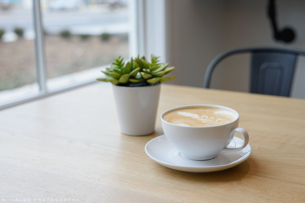Cozy setting with a latte. Roost Darien, small business photos by N. Lalor Photography.