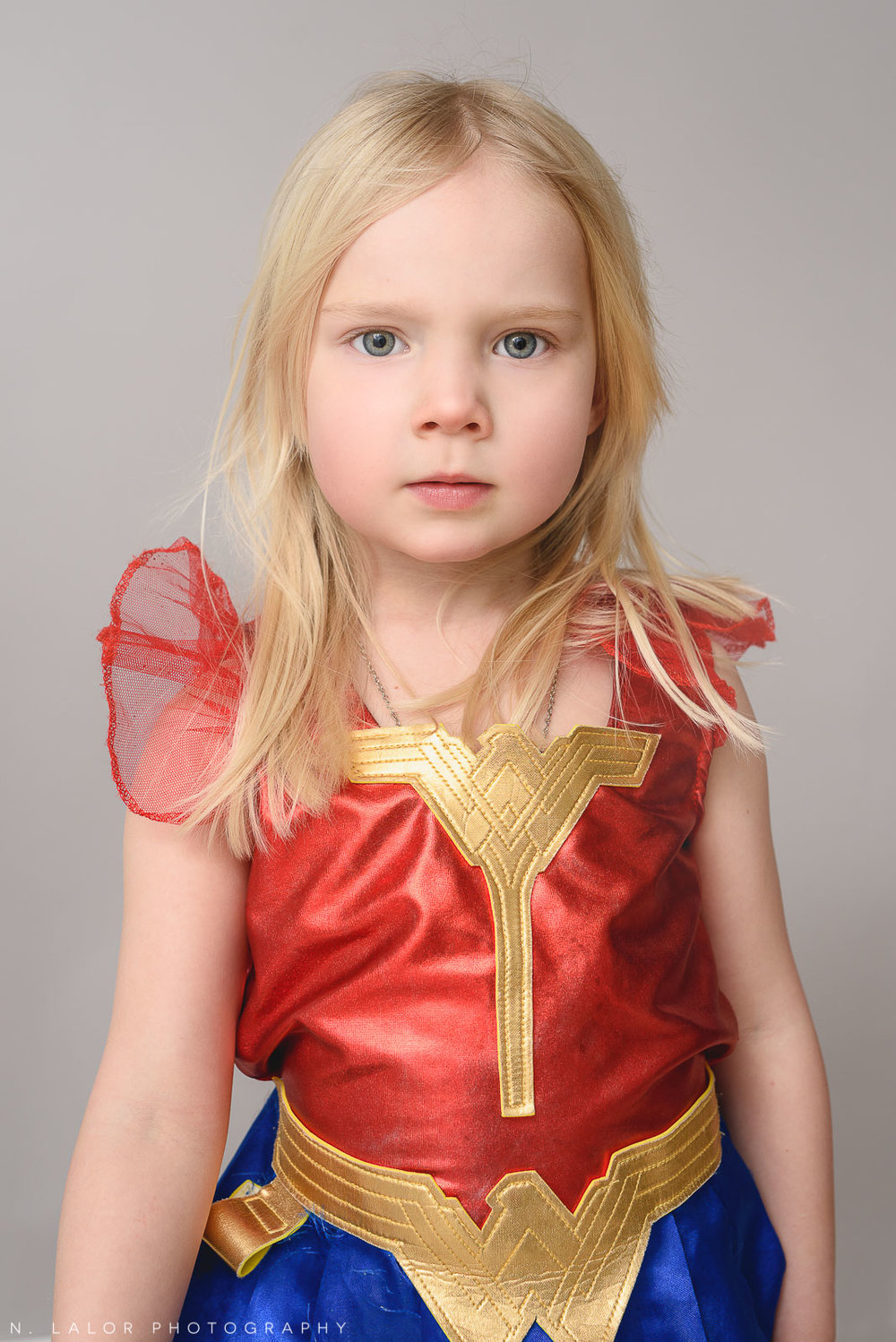Little girl dressed in a Wonder Woman costume. Studio portrait by N. Lalor Photography in Greenwich, Connecticut.