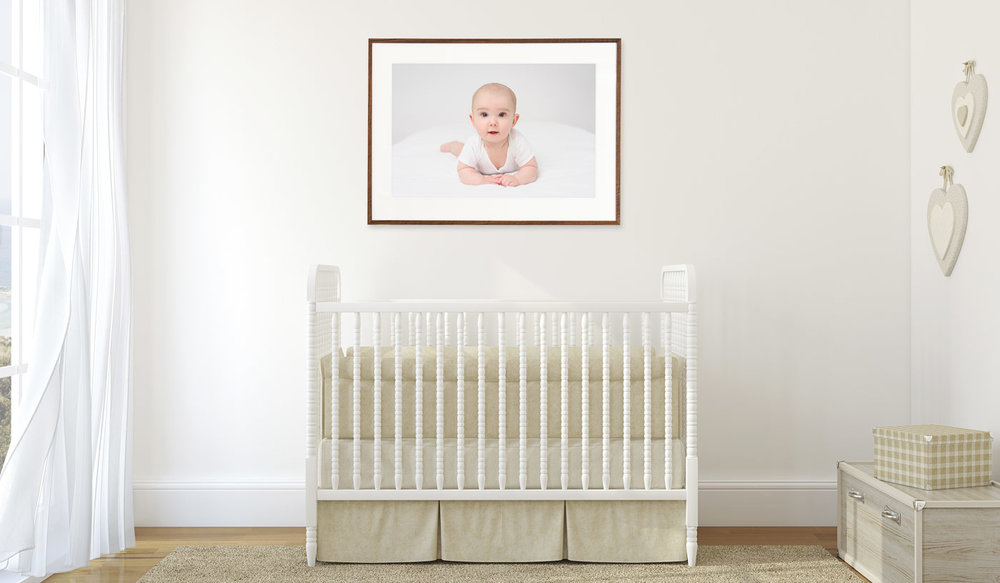 "Image of a 20x30"" framed print of a baby, displayed in a nursery above the crib."
