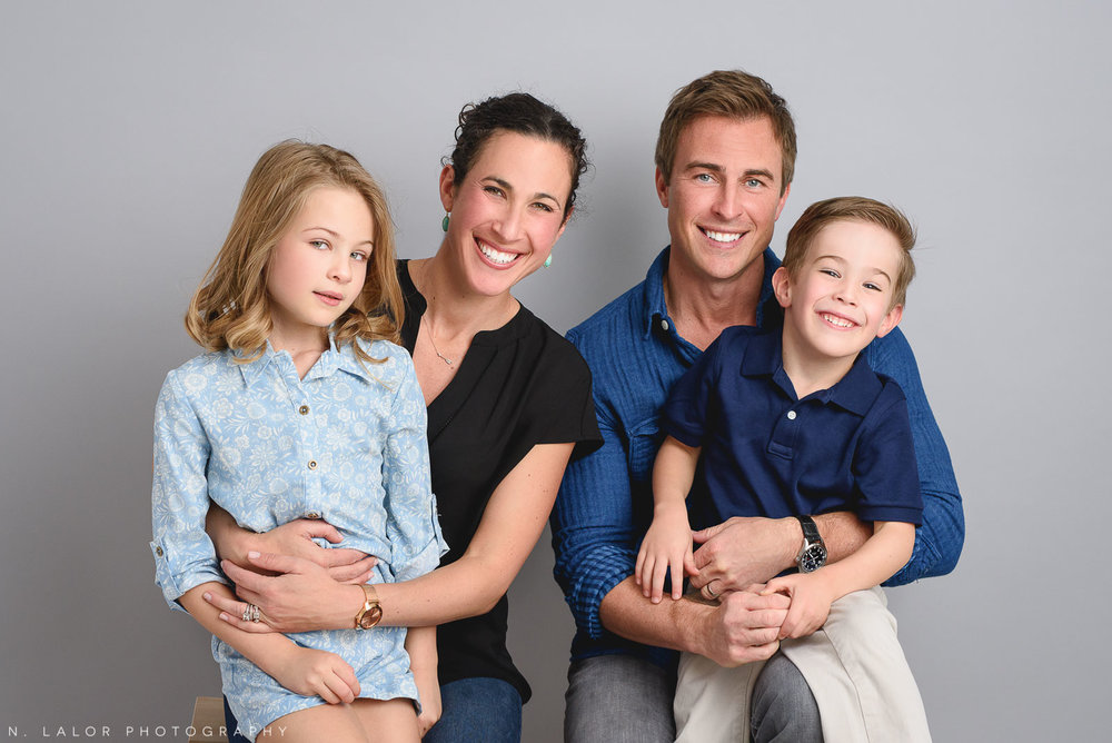 Family wearing shades of blue and black. Studio portrait by N. Lalor Photography in Greenwich, Connecticut.