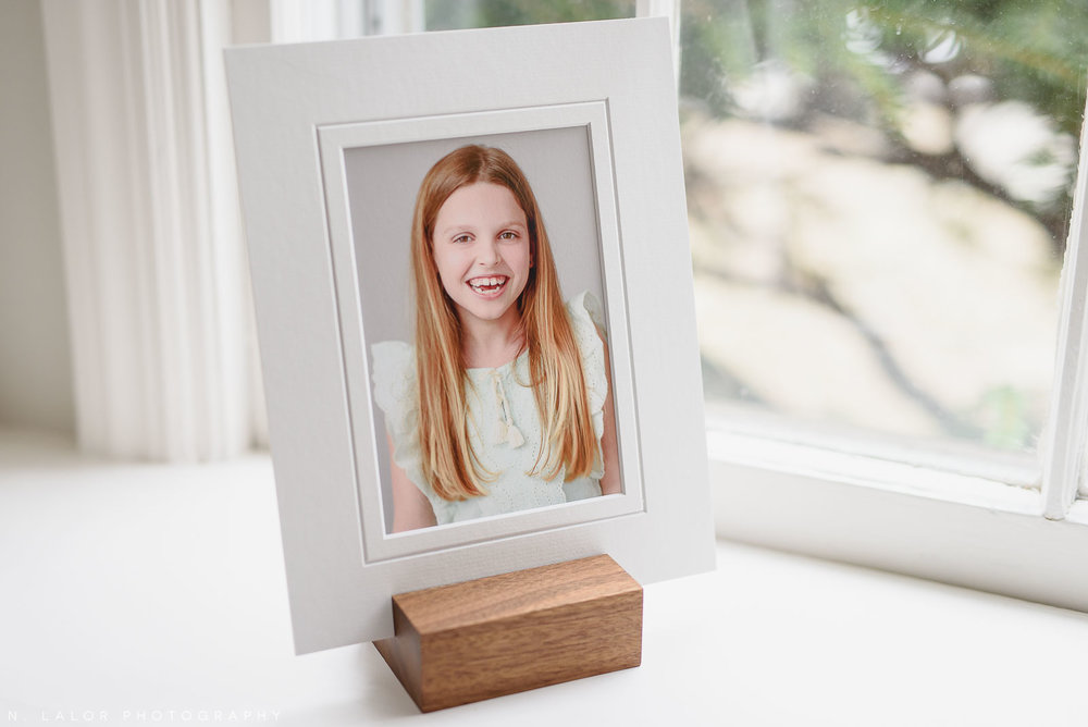 Image of a matted fine art print, displayed in a wooden photo stand made out of solid walnut. Photography by N. Lalor Photography.