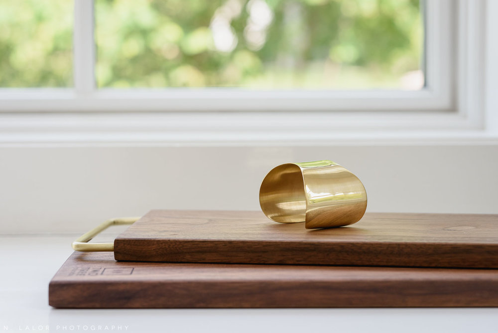 Sustainably-sourced gold bracelet and wood cutting boards. Local Small Business photoshoot for METTA10 by N. Lalor Photography. Westport, Connecticut.
