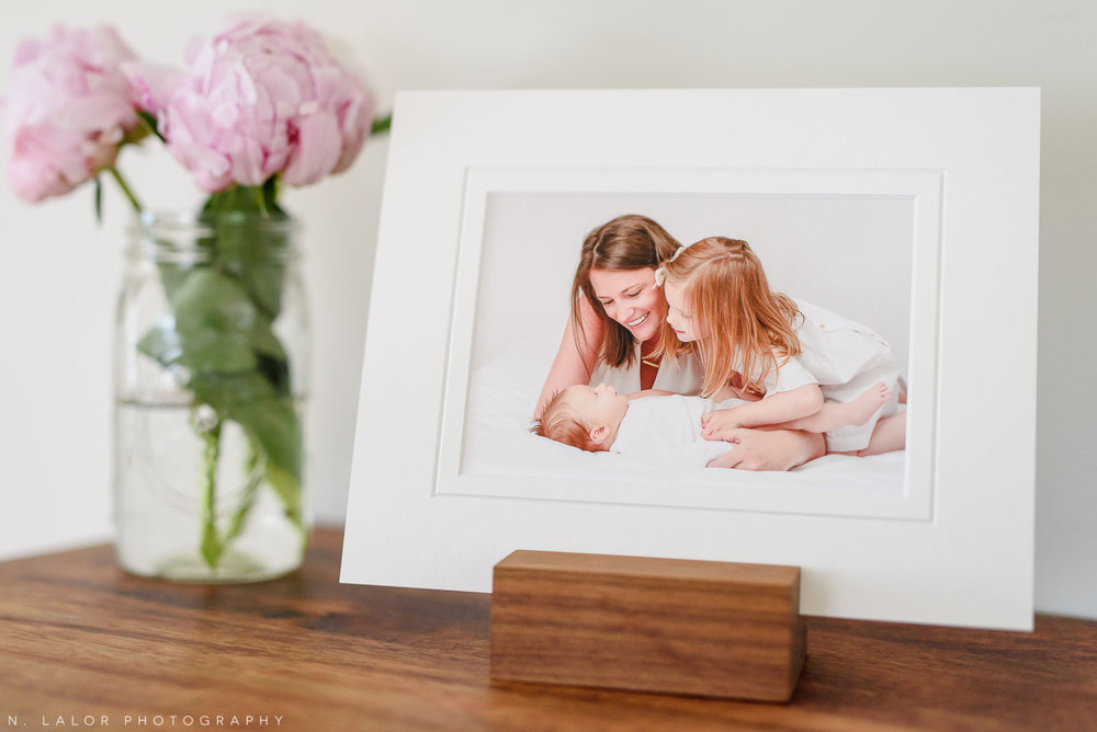 Image of a tabletop with a matted print displayed in a wooden photo stand. Portrait by N. Lalor Photography in Greenwich, Connecticut.