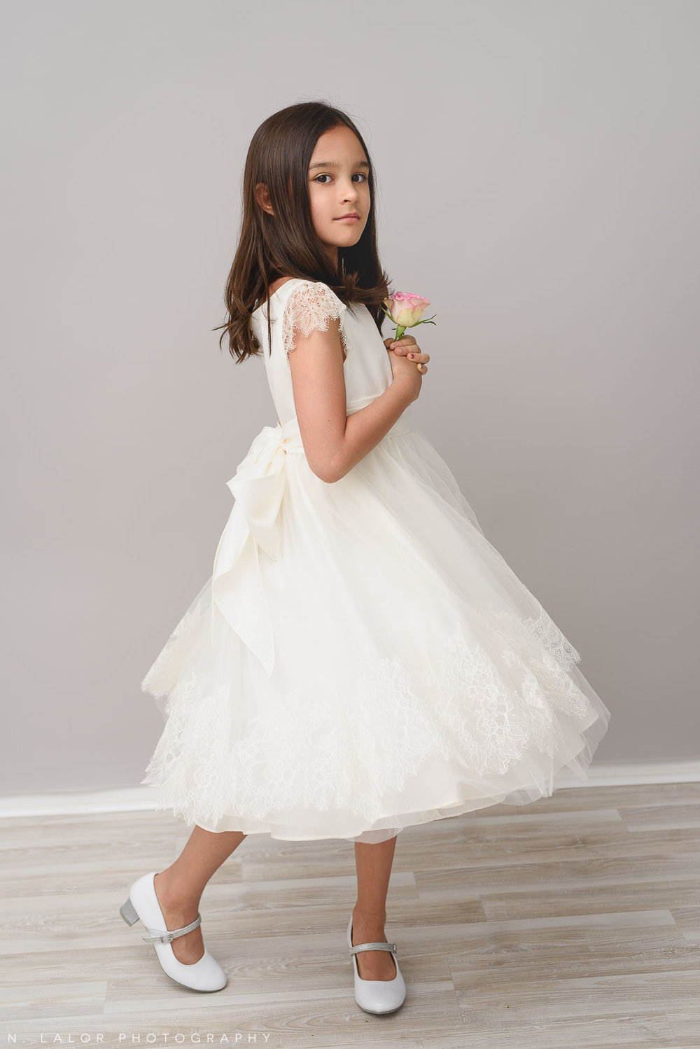 Photograph of an 8-year old girl in a white dress. Studio portrait by N. Lalor Photography. Greenwich, Connecticut.