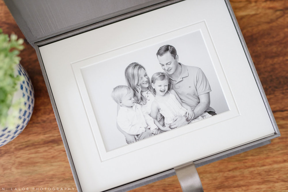 Image of a matted fine art print showing a black and white photograph of a family laughing. Studio portrait by N. Lalor Photography. Greenwich, Connecticut.
