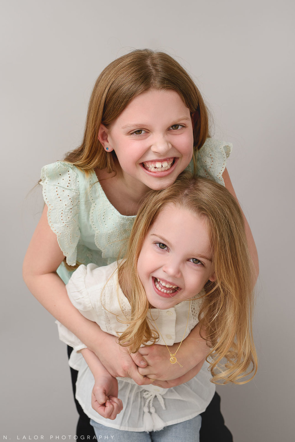 Image of two sisters laughing. Studio portrait by N. Lalor Photography in Greenwich, Connecticut.