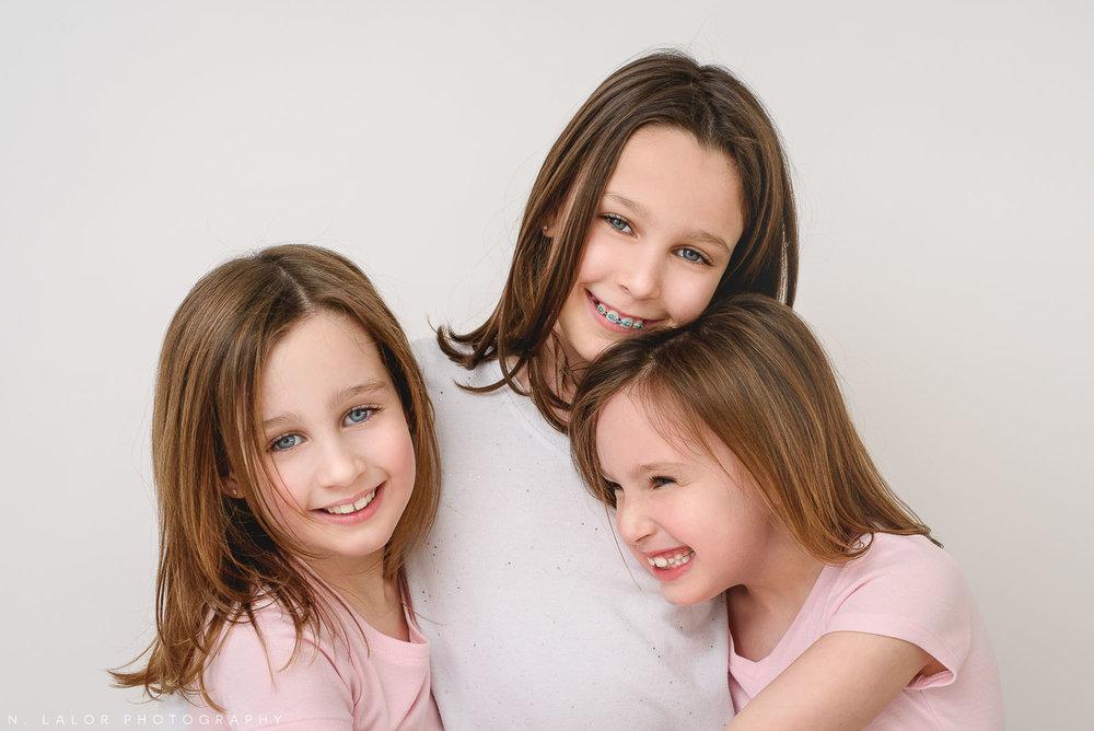 Image of three sisters hugging. Studio portrait by N. Lalor Photography in Greenwich, Connecticut.