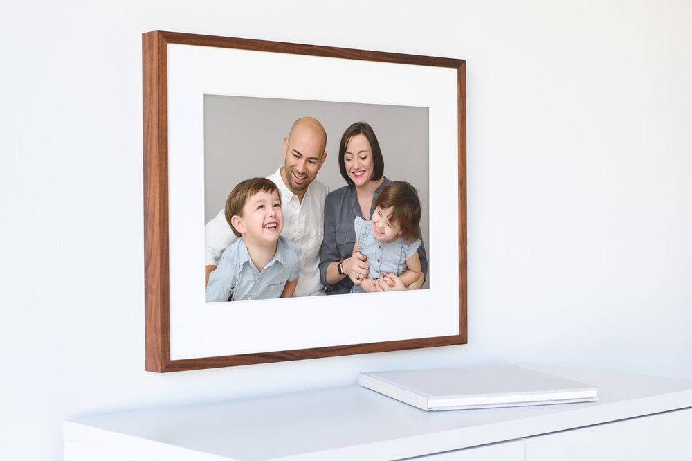 Image of a large printed frame showing a happy laughing family.Studio portrait by N. Lalor Photography in Greenwich Connecticut.
