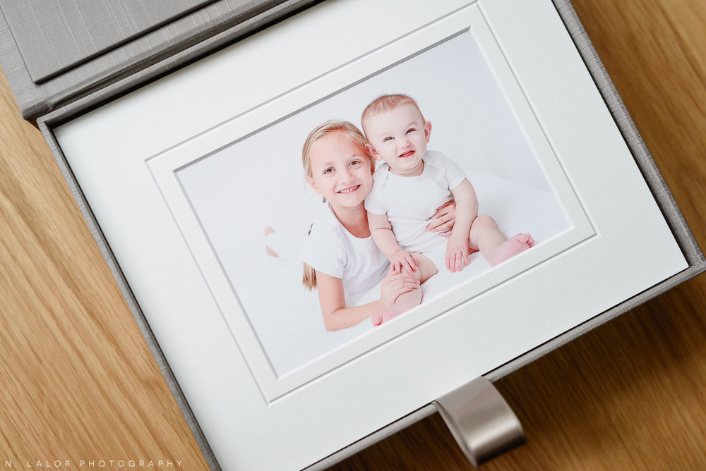 Image of a heirloom presentation box filled with museum-quality prints from a family photo session. Portrait of girl siblings by N. Lalor Photography in Greenwich Connecticut.