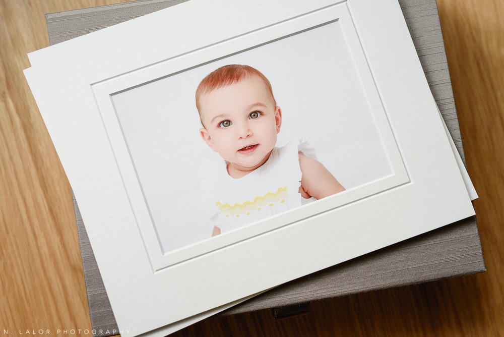 Image of a fine art print in a white mat. Portrait of a baby by N. Lalor Photography in Greenwich Connecticut.