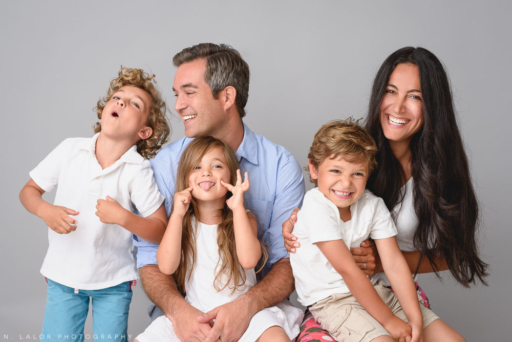 Image of a happy silly family with three kids. Studio portrait by N. Lalor Photography in Greenwich Connecticut.