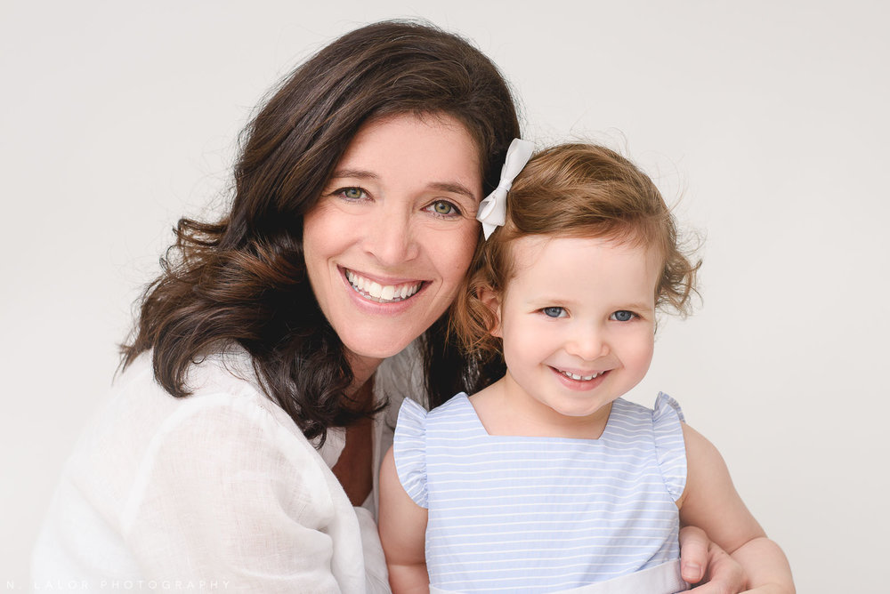Image of a Mom and her 2-year old daughter, smiling. Studio portrait by N. Lalor Photography in Greenwich Connecticut.