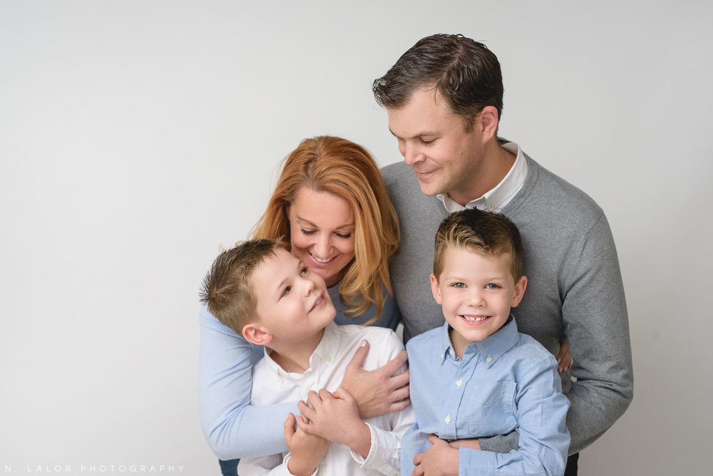 Image of a happy family, smiling at each other. Studio portrait by N. Lalor Photography in Greenwich, Connecticut.