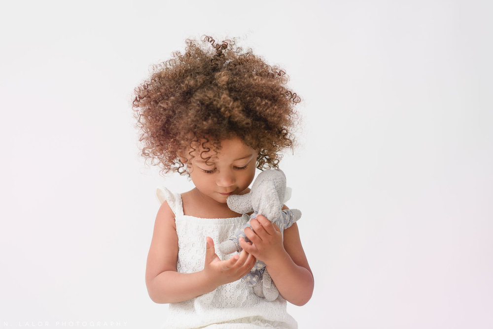 Image of a toddler with her stuffed toy. Portrait by N. Lalor Photography in Greenwich, Connecticut.