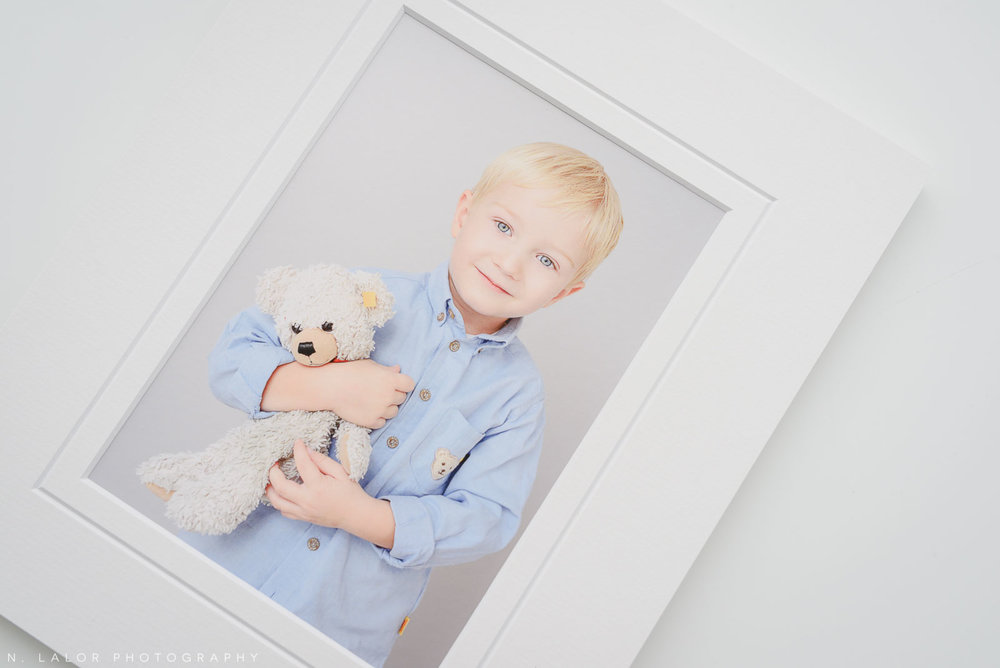 Image of a printed portrait of a happy boy with his stuffed teddy bear. Studio child portrait by N. Lalor Photography in Greenwich, Connecticut.