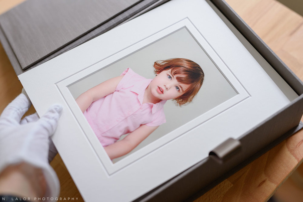 Image of a matted print going into a family heirloom presentation box. Portrait by N. Lalor Photography in Greenwich, Connecticut.