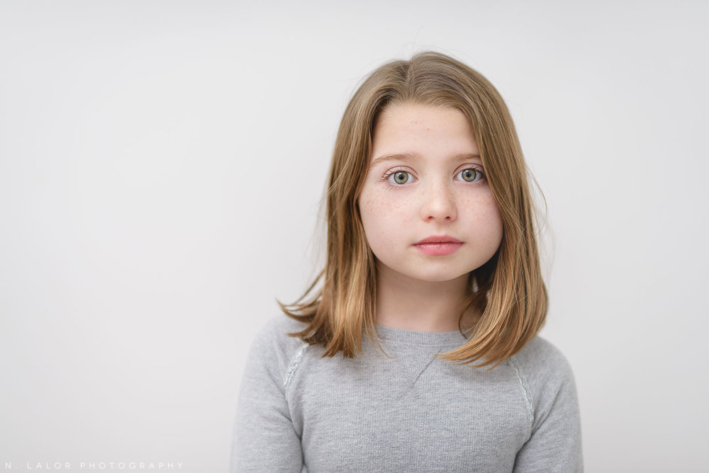 Simple and funny image of an 8-year old girl. Studio portrait by N. Lalor Photography in Greenwich Connecticut.
