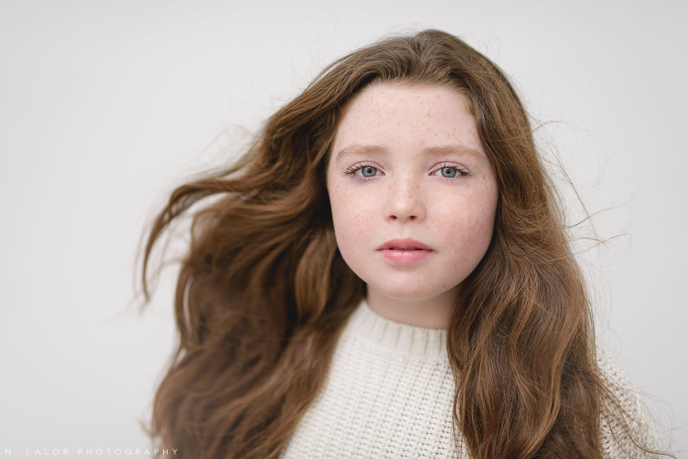 Photo of a tween girl with hair blown by a fan. Studio portrait by N. Lalor Photography in Greenwich, Connecticut.