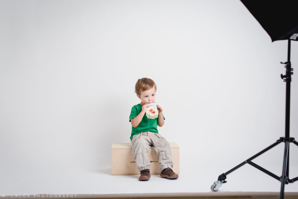 Behind the scenes image of a child being photographed in a Studio. N. Lalor Photography in Greenwich, Connecticut.