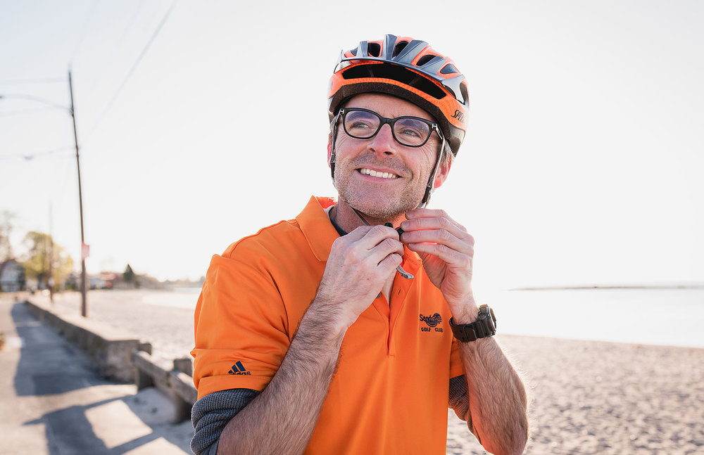 Image of a man buckling his bicycle helmet. Lifestyle personal branding portrait by N. Lalor Photography. Serving Fairfield County, Connecticut.