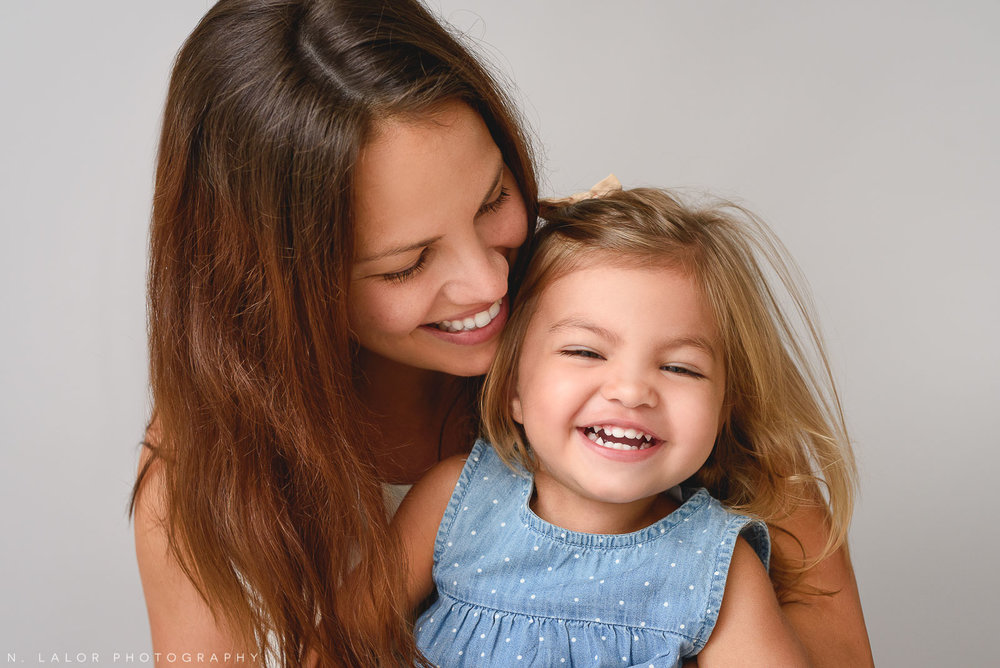 Image of a Mom laughing with her toddler girl. Studio family portrait by N. Lalor Photography in Greenwich Connecticut.