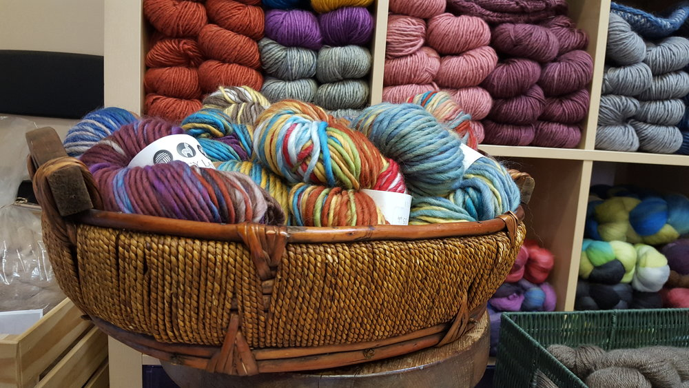 Kitchen Sink Lopi from Legacy Lane Fiber Mill in New Brunswick in the basket. Suri Singles from Salt River Mills on the shelf.
