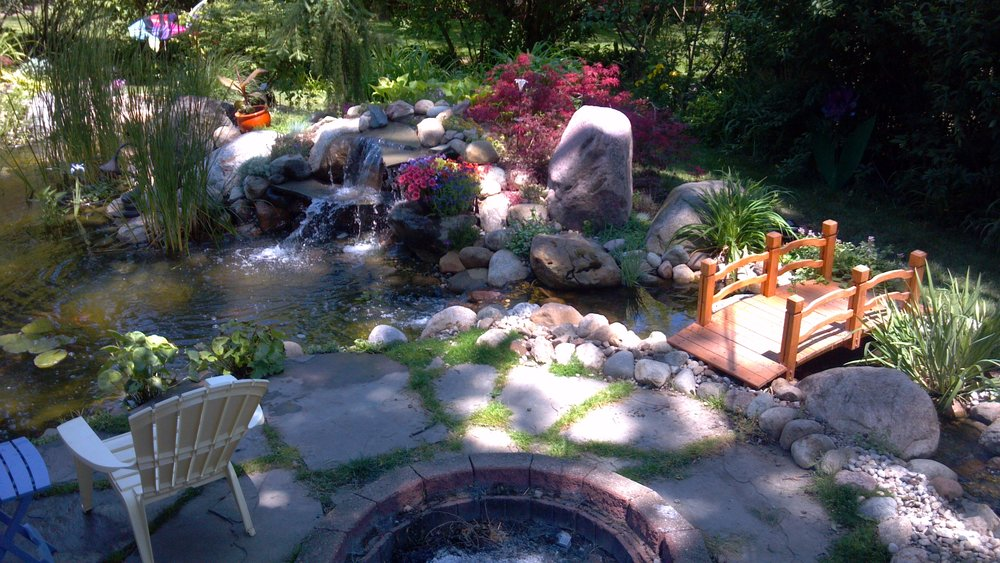 This family wanted it all! A storybook bridge over a meandering stream, flowing into a koi pond. Enjoyable day or night with the added bluestone patio and fire ring.