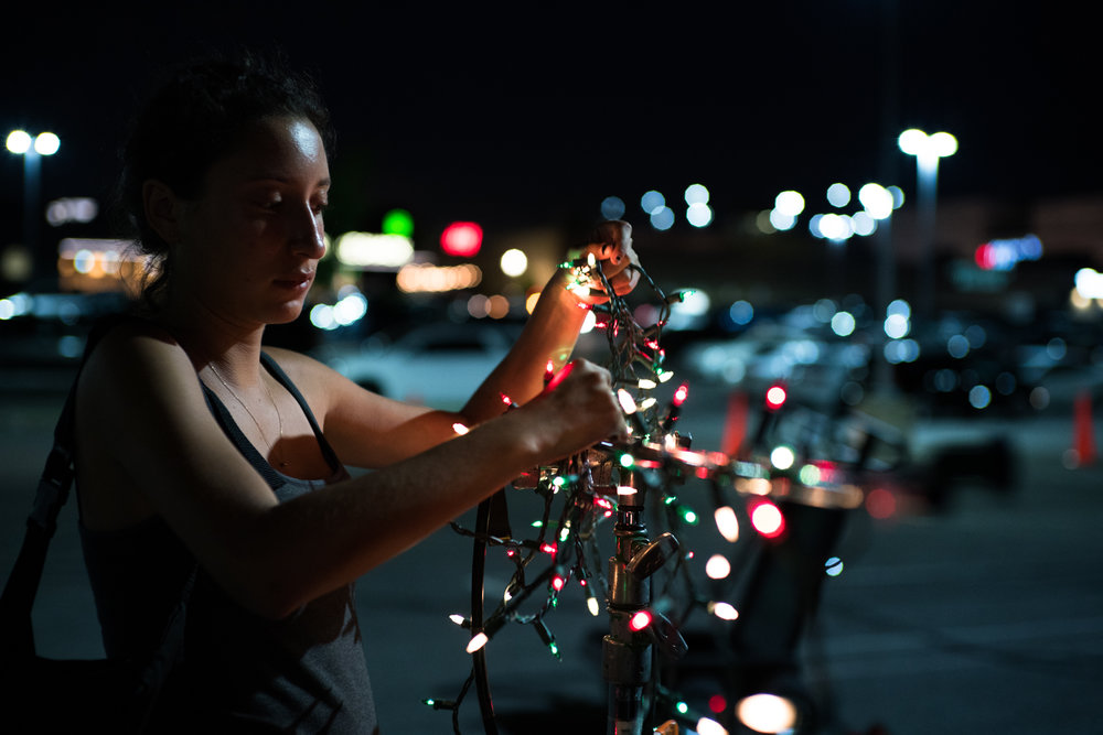 Production designer Emma Verner wraps some christmas lights around a stand for some traffic-light bokeh