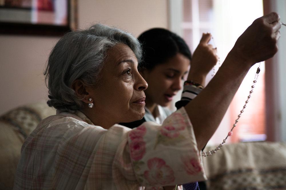 Mami (Awilda Santana) and Naya (Crystal de la Cruz) pray for their favorite team