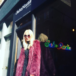 Jennie rocks a scarlet faux fur jacket for her interview at Soho Radio, London.