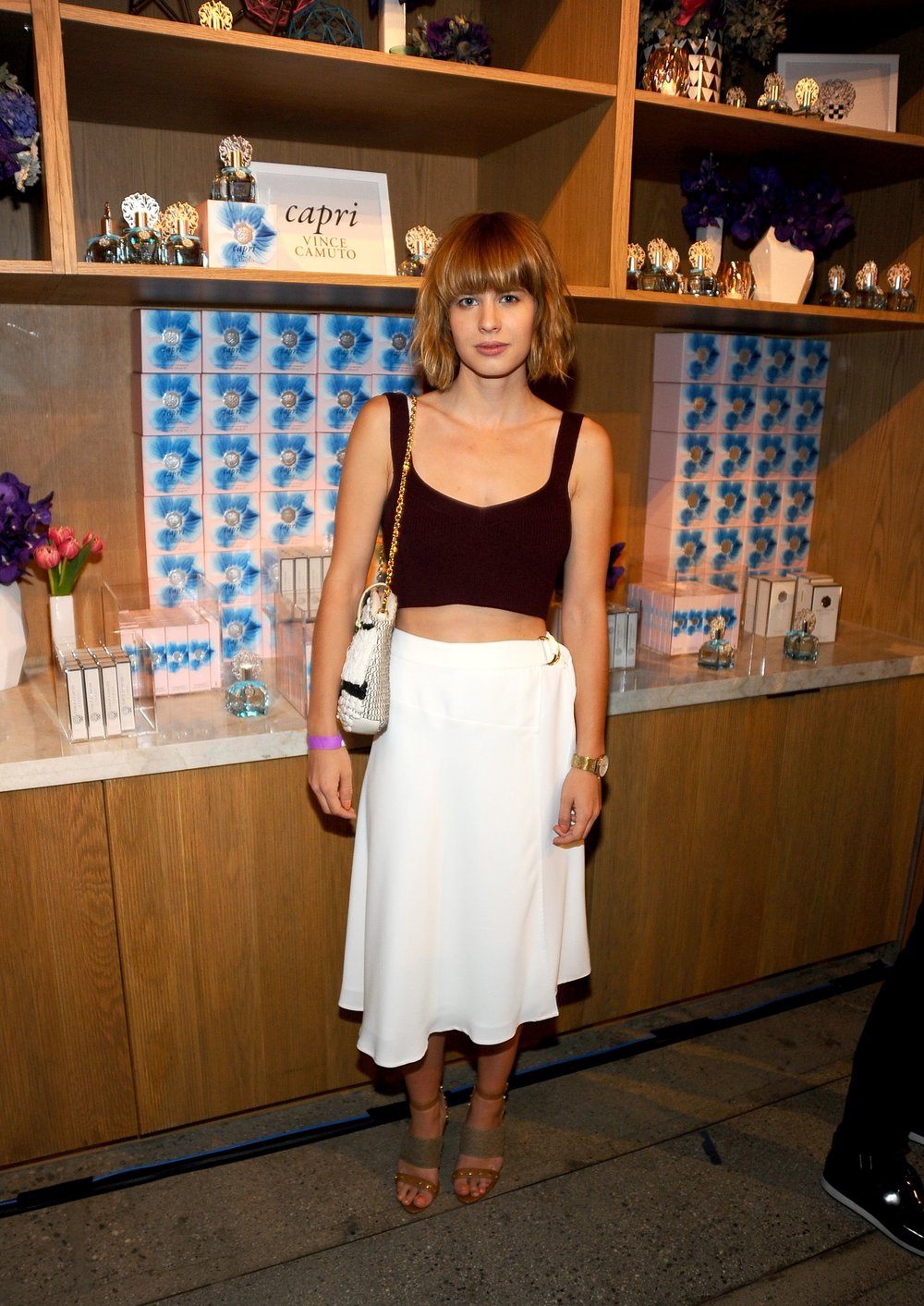 Lisa Dengler,  Just Another , wears a Vince Camuto White Wrap Skirt, Louise et Cie Kellyn Heels and carries a Fae Clutch.