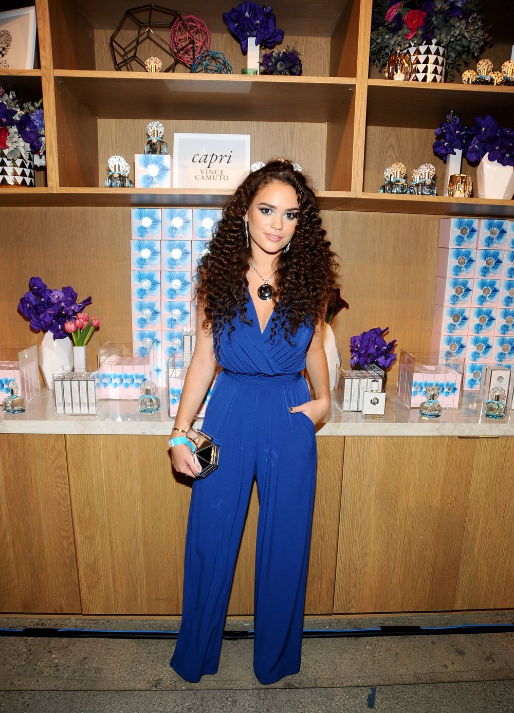 Madison Pettis wears a Vince Camuto jumpsuit and necklace, Imagine Vince Camuto Keir Heels and carries the Vince Camuto Aleni Clutch.
