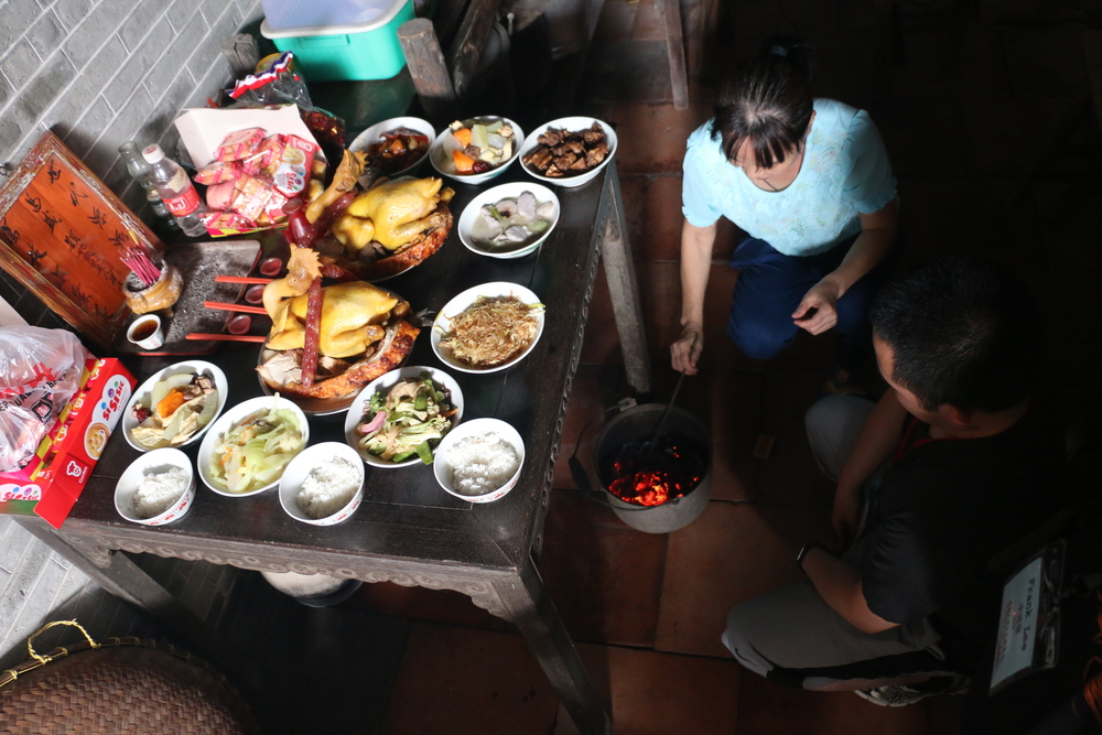 burning paper money in front of a table of food offerings.