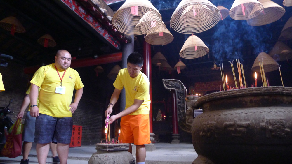 Lighting incense within the ancestral temple.
