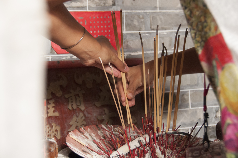 My aunt Ling Yi guides me as I place the incense.