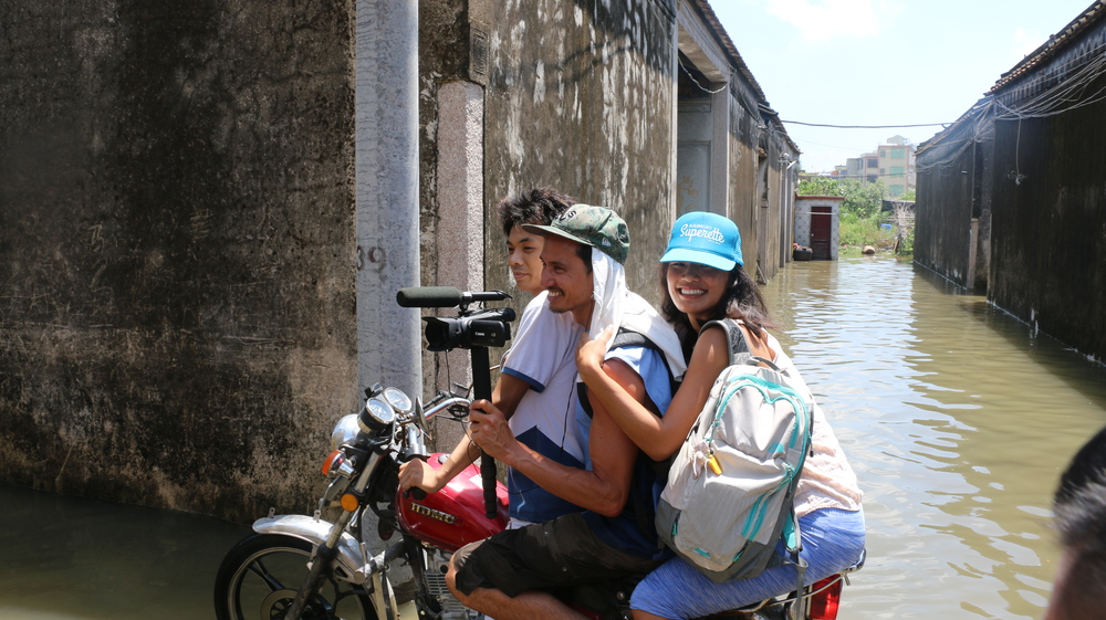 Gino & Linda braving the flood to record my maternal village
