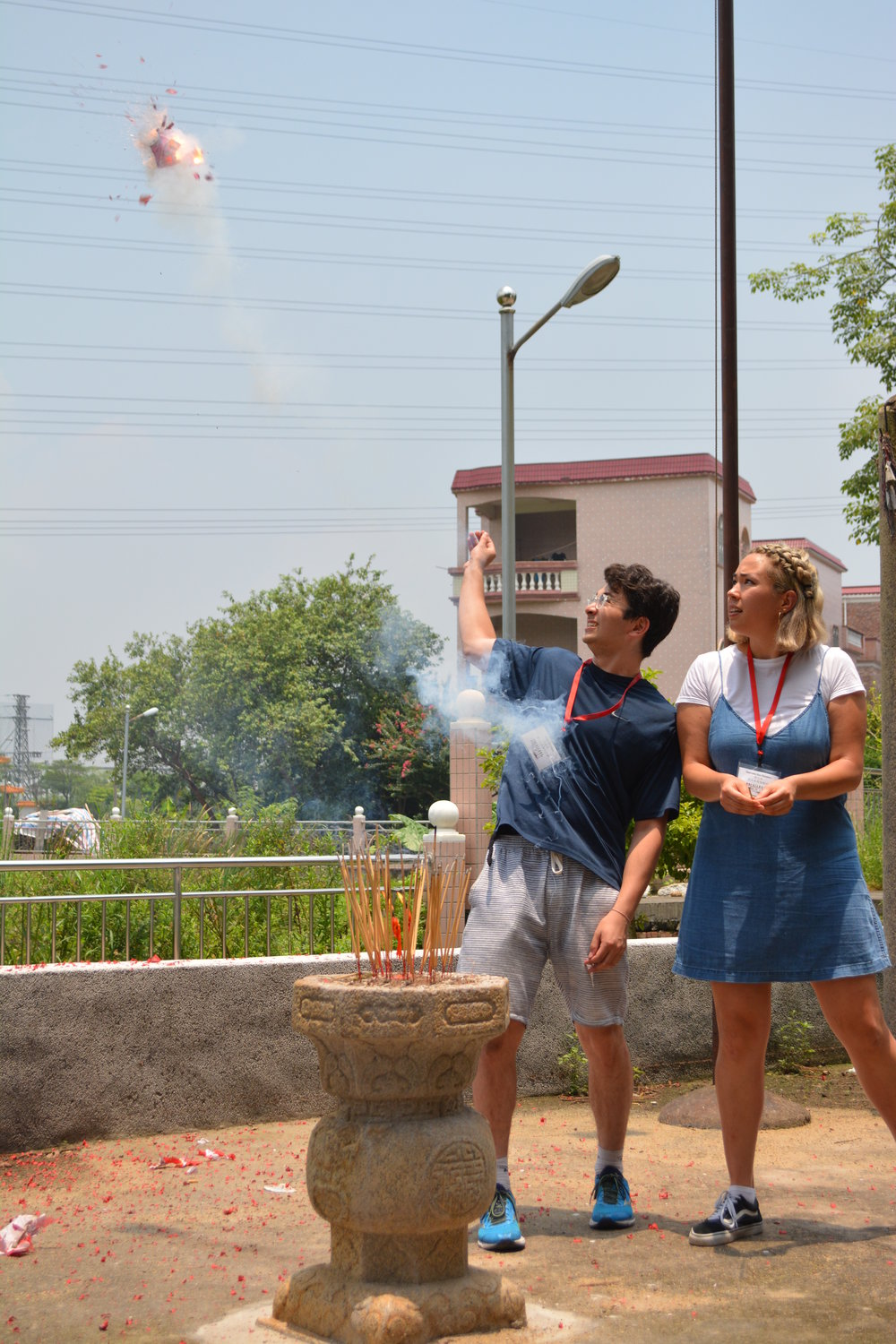 Cousins Olly Goodman and Gaby Koc-Spadaro throwing firecrackers at their grandmother's village in Sanshui