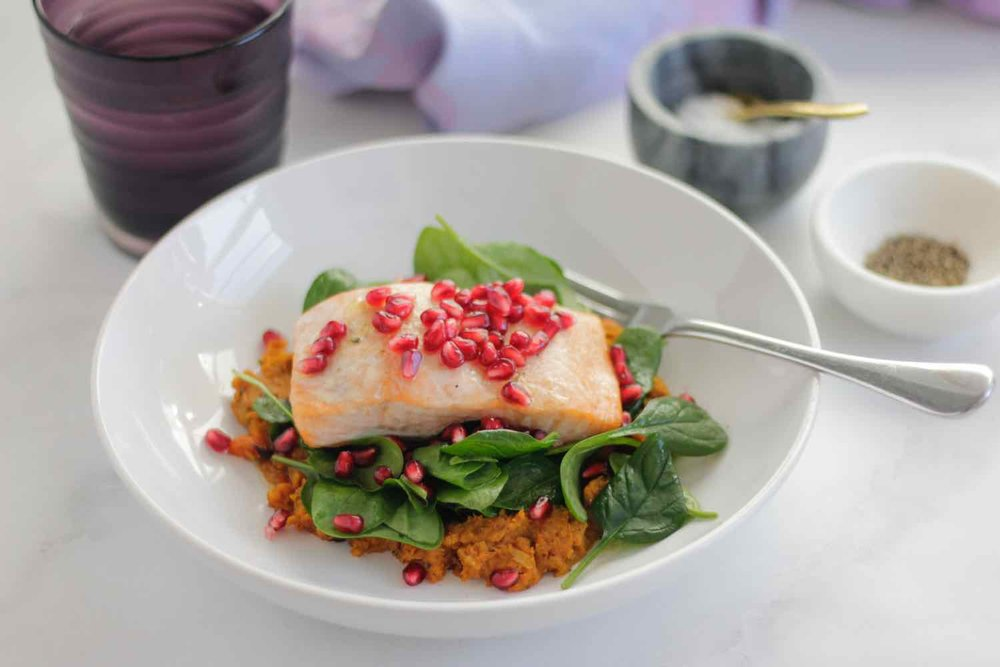 Steamed salmon on bed of smashed pumpkin with chickpeas and cumin