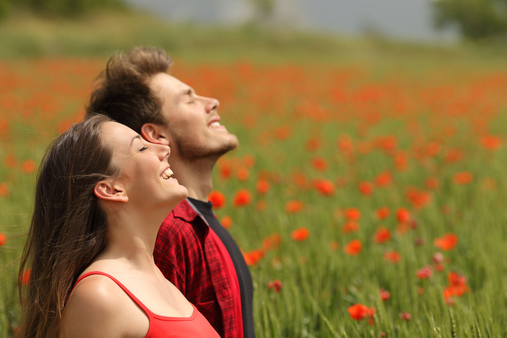 Happy couple breathing fresh air in a red field.jpg